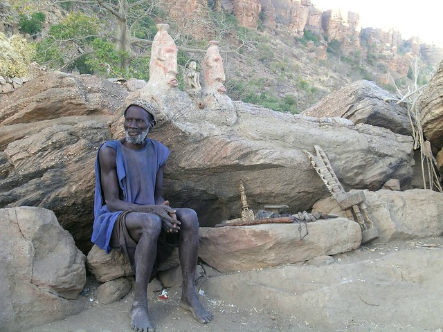 An elder of dogon tribe sitting near a traditional altar