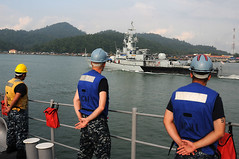 LUMUT, Malaysia (May 16, 2011) Sailors aboard USS Avenger (MCM 1) stand at parade rest as the ship passes alongside the Royal Malaysian Navy ship KD Laksamana Tan Pusmah (F137). (U.S. Navy photo by Mass Communication Specialist 3rd Class Brian A. Stone)