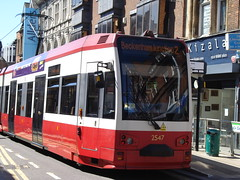 """A red-and-white tram with """"Beckenham Junction 2"""" showing on the front dot-matrix display. The number """"2547"""" is on the front of the tram. A shop called """"Kizala"""" is visible behind the tram, as is a banner reading """"Allders"""" on the upper floors of some shops further back."""