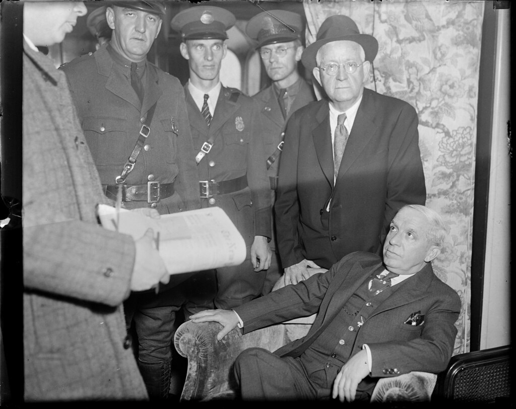 Charles Ponzi surrounded by policemen in hotel, awaiting deportation