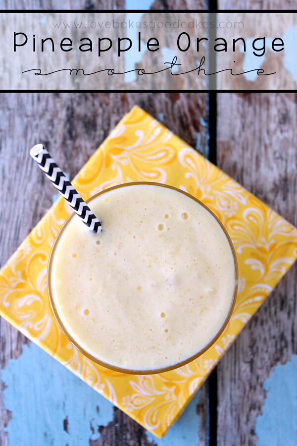 Pineapple Orange Smoothie in a glass with a straw.