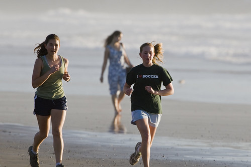 Two female girls jogging on the sand beach in late evening light