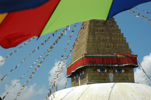 Sunny day with puffy clouds as the eyes oversee new prayer flags beings raised. Shot from a restaurant across from the Bodha Stupa, under an umbrella, Kathmandu, Nepal by Wonderlane