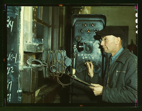 Hump master in a Chicago and Northwestern railroad yard operating a signal switch system which extends the length of the hump track. He is thus able to control movements of locomotives pushing the train over the hump from his post at the hump office; Chic by The Library of Congress