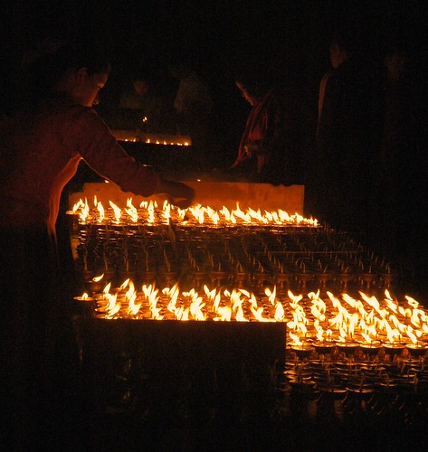 Butter lamps and Candles for offering, street, Boudha, Kathmandu by Wonderlane