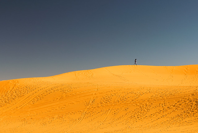 A berber walking along the Erg Chebbi sand dunes in Morocco.