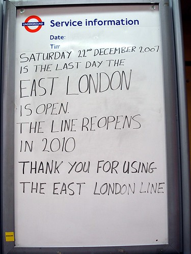 "A whiteboard with the London Underground roundel in the top left-hand corner and the heading ""Service information"" printed at the top. Handwritten text below reads: ""Saturday 22nd December 2007 is the last day the East London is open. The line reopens in 2010. Thank you for using the East London Line."""