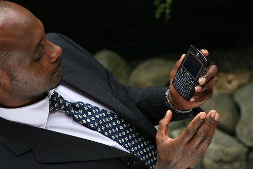 Businessman using Windows Mobile device with rocks in background