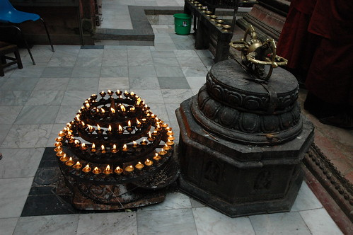 "Mandala candle offering (4 tiered) with large dorje (vajra) on a pedestal, marble floor, monks robes, Mahabuddha Temple, also known as ""temple of thousand buddhas"", skikhar style buddhist temple, Kathmandu, Nepal by Wonderlane"