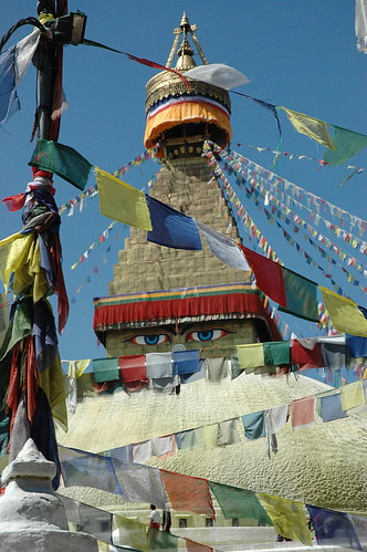 Among Tibetan Buddhist prayer flags, overseen by the eyes of Lord Buddha, people walking on the mandala section of the Jarung Kashor (bya rung kha shor) the Great Stupa at Boudhanath, Kathmandu, Nepal by Wonderlane