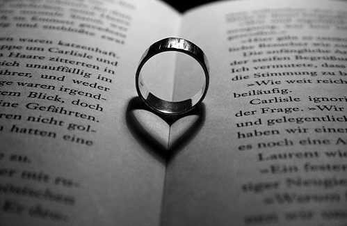 Photograph of ring in open spine of book, casting shadow of a heart