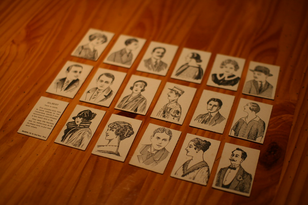 Antique head-and-shoulders line drawings laid out in grid on wooden table