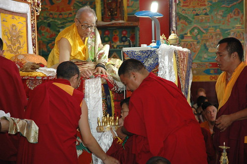With the help of senior lamas, a very young lama HE Asanga Rinpoche preparing to offer the Mandala of the Universe to his grandfather, HH Jigdal Dagchen Sakya, Tharlam Monastery, Nepal by Wonderlane