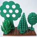 Three vintage Lego trees and a modern shrubbery