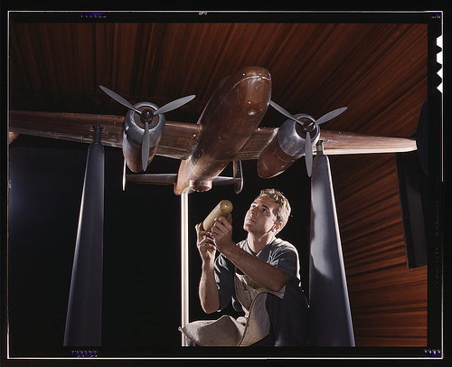 An experimental scale model of the B-25 plane is prepared for wind tunnel tests in the plant of the North American Aviation, Inc., Inglewood, Calif. The model maker holds an exact miniature reproduction of the type of bomb the plane will carry. This plant by The Library of Congress