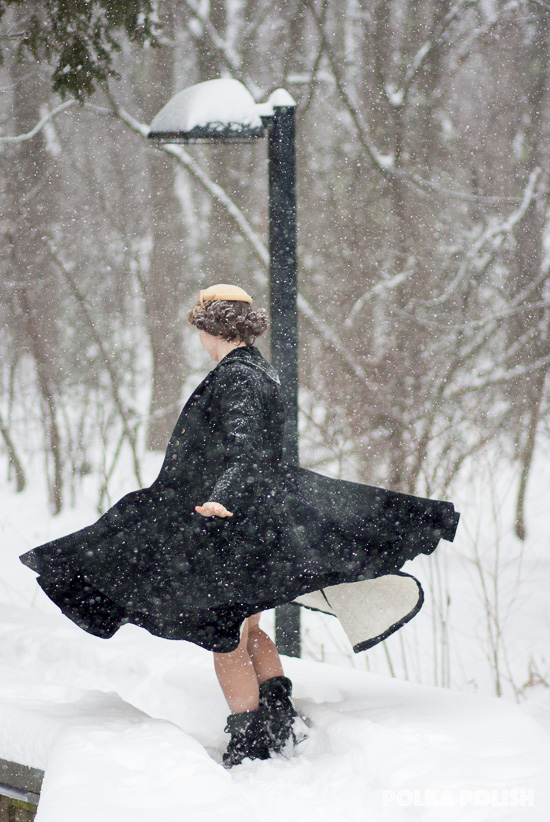 1950s inspired outfit with a perfect for twirling black coat and skirt paired with a tan hat on a snowy winter day