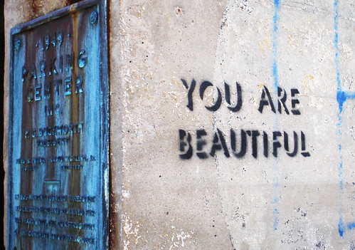 """Image Description: a wall with a bright blue door. On the side of the wall is graffittied in stencil """"You are Beautiful."""""""