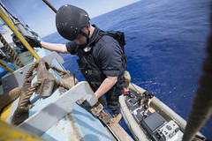 Fire Controlman 2nd Class James Masterson disembarks a fishing vessel Feb. 8 during an Oceania Maritime Security Initiative (OMSI) boarding mission. (U.S. Navy/MC3 Danny Kelley)