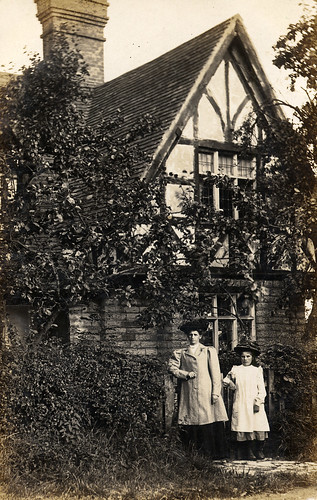 Mother and daughter in front of timber-framed house