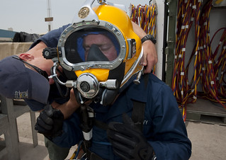 Navy diver ensures a proper seal on the Kirby Morgan 37 diving helmet on another diver