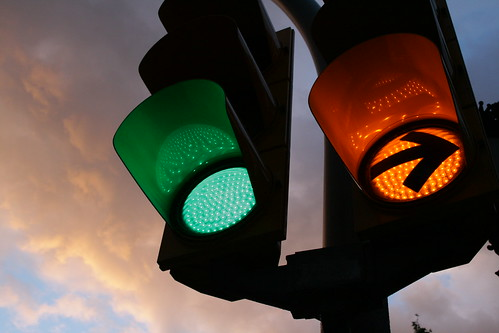 Traffic lights: one green lamp and one orange right-turn arrow.