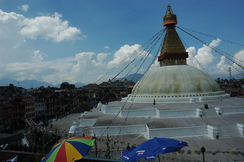 Sunny day, cafe umbrellas, puffy clouds, the circle of the town, Bodha Stupa, Kathmandu, Nepal by Wonderlane