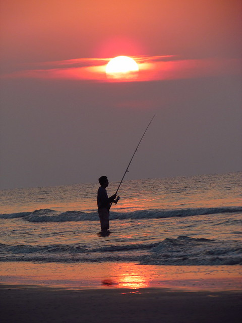 man surf fishing at sunrise in hilton head island south