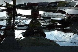 Dark and faithful Tibetan Buddhist prayer flags in a stiff wind, Boudha Stupa, Kathmandu, Nepal