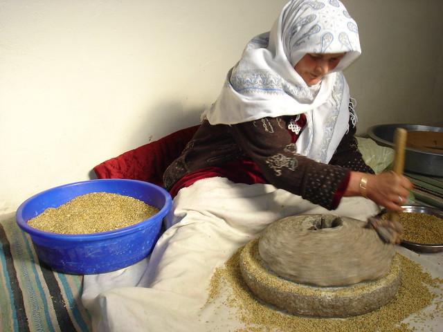 Yamma grinding grain on a quern stone made in Ah Frah! الوالدة تطحن القمح لعمل الفريك