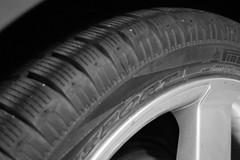 bumper(0.0), tire(1.0), automotive tire(1.0), automotive exterior(1.0), wheel(1.0), synthetic rubber(1.0), tread(1.0), rim(1.0), monochrome photography(1.0), alloy wheel(1.0), monochrome(1.0), black-and-white(1.0), spoke(1.0),