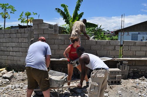 Volunteers mixing cement and placing bricks for security wall