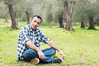 Mature italian man sitting on the grass under olive trees