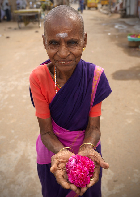 Shaved woman selling flowers near a temple - India