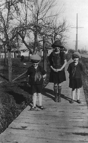 Three children on a boardwalk