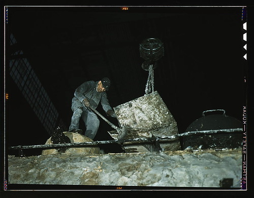Spreading asbestos mixture on boiler of a locomotive at the C & NW RR 40th Street locomotive shops  (LOC)