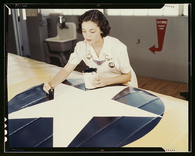 Painting the American insignia on airplane wings is a job that Mrs. Irma Lee McElroy, a former office worker, does with precision and patriotic zeal. Mrs. McElroy is a civil service employee at the naval Air Base, Corpus Christi, Texas. Her husband is a f