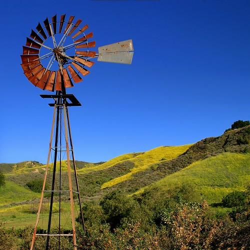 ranch old blue light sky west color green tower history mill nature water windmill field wheel yellow metal rural america vintage circle landscape landscapes energy technology power wind outdoor antique farm country stock working property villages pump american western land fields rotation tall tradition plain alternative renewable rotate stockphotography microstock landscapesofvillagesandfields