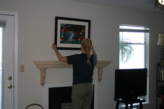 Mom hangs the picture over the unpainted mantel