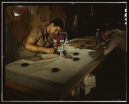 The utmost precision is required of these operators who are cutting and drilling parachute packs in an eastern factory, Manchester, Conn. Their work is under constant close supervision. Pioneer Parchute Company  (LOC)
