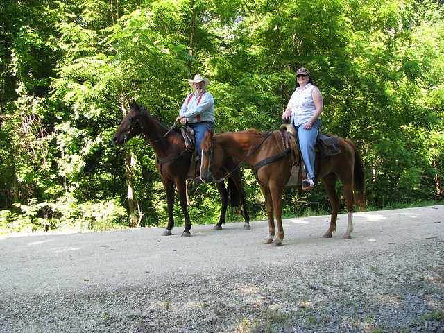 A couple and their horses enjoying the trail.