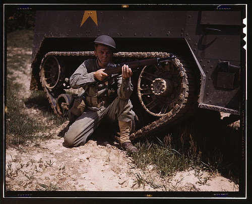 A young soldier of the armored forces holds and sights his Garand rifle like an old timer, Fort Knox, Ky. He likes the piece for its fine firing qualities and its rugged, dependable mechanism. Infantryman with halftrack  (LOC)