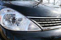 wheel(0.0), automobile(1.0), automotive exterior(1.0), vehicle(1.0), nissan tiida(1.0), grille(1.0), bumper(1.0), land vehicle(1.0),