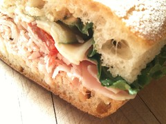 focaccia(0.0), sandwich(1.0), lunch(1.0), ham and cheese sandwich(1.0), baked goods(1.0), muffuletta(1.0), ciabatta(1.0), food(1.0), dish(1.0), cuisine(1.0),