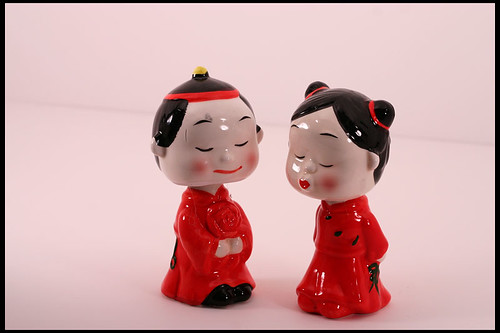 Small porcelain dolls showing a Chinese husband and wife in traditional red clothing