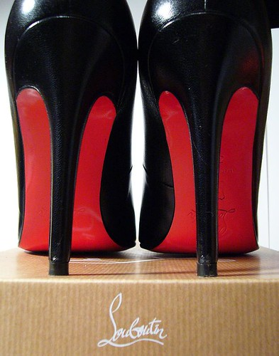 Loubotins on top of box showing red soles.
