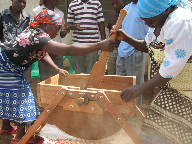 Two women use a machine to shell peanuts.