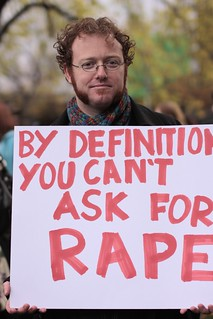 A man with dark ginger hair and whiskers is holding a sign which says BY DEFINITION YOU CAN'T ASK FOR RAPE