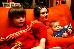 mother and sons curled up on the couch, watching a m…