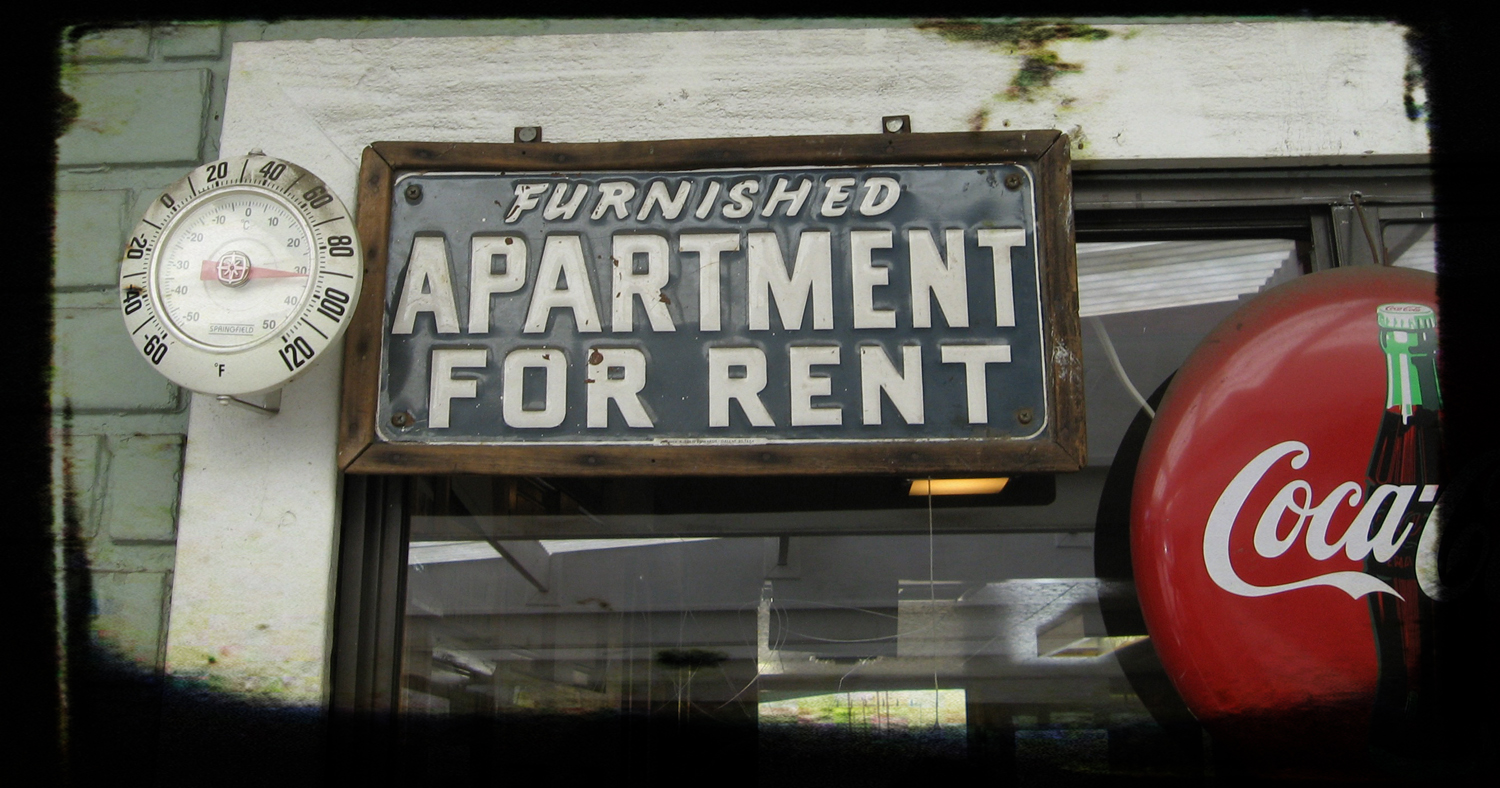 "Thermometer, sign that says ""furnished apartment for rent,"" and Coca-Cola sign, all hanging in window"