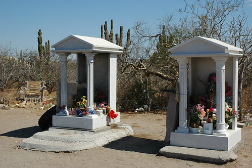 Roadside shrines in greek style, candles, statues, tire, trees, cactus, desert, abandoned armchair, Armchair philosophy; All the comforts of home, roadside worship area, worn out armchair in the desert, near La Paz, Baja California Sur, Mexico by Wonderlane